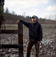 Hired ranch hand Jake Knox stands in the mud he works in everyday in the South Seattle suburb of Maple Valley.