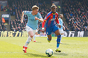 Manchester City midfielder Kevin De Bruyne (17) and Crystal Palace forward Wilfried Zaha (11) during the Premier League match between Crystal Palace and Manchester City at Selhurst Park, London, England on 14 April 2019.