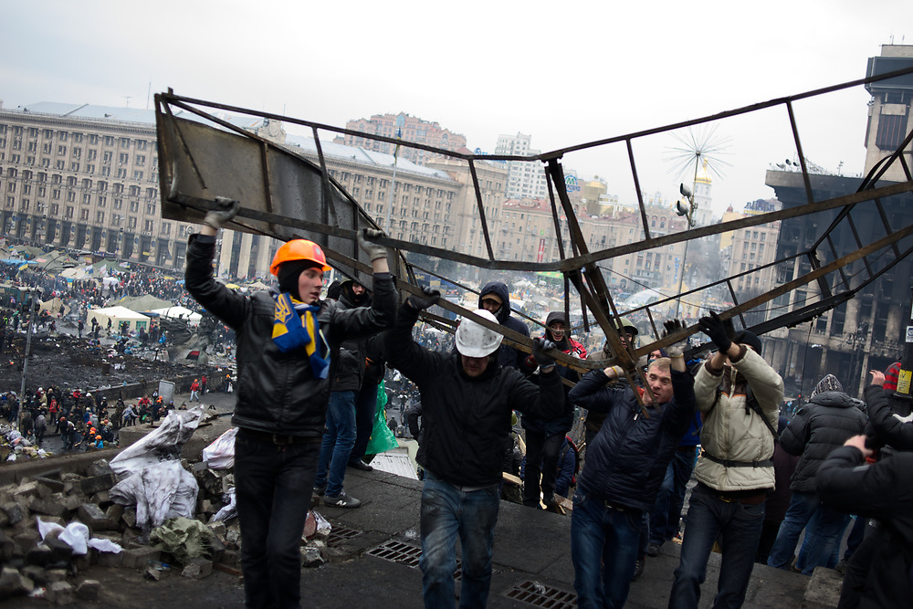 KIEV, UKRAINE - February 20, 2014: Anti-government protestors carry scrap metal to be used in new defensive barricades, as violent clashes between protestors and riot police happen outside Independence Square in central Kiev. The riot police responded to the advance with gunfire that, according to the opposition, killed at least 70 and as many as 100 people. The drastic escalation of the three-month-old Ukraine crisis left the country reeling from the most lethal violence in decades. CREDIT: Paulo Nunes dos Santos