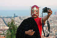 A paledor (wrestler), making a promotion video of himself, high up in the city of Barcelona.