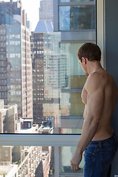 shirtless man in an apartment in New York City looking out a large glass window