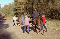 Women with visual impairments riding horses with helpers,