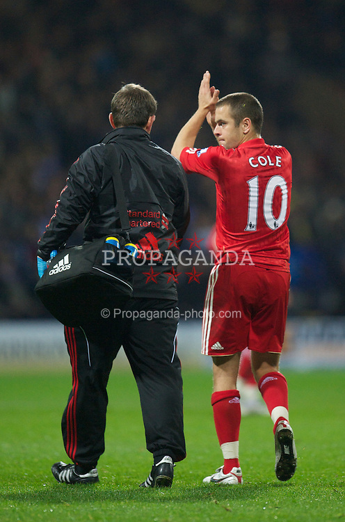 BOLTON, ENGLAND - Sunday, October 31, 2010: Liverpool's senior physiotherapist Rob Price checks walks off with injured Joe Cole during the Premiership match against Bolton Wanderers at the Reebok Stadium. (Pic by: David Rawcliffe/Propaganda)