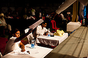 Razia Shabnam hands the referee her score sheet as she judges a bout at an all-India invitational boxing competition in the neighbouring town of Burnpur, Calcutta, West Bengal, India. Razia Shabnam, 28, was one of the first women boxers in Kolkata. She was also the first woman in her community to go to college. She is now a coach and one of only three international female boxing referees in India. Photo by Suzanne Lee for Panos London