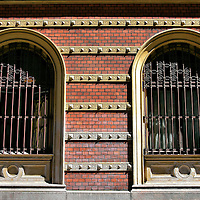 Arched Windows at Östergatan 32 in Malmö, Sweden <br /> These two arched windows are on an ornate building at Östergatan 32. The street dates back to the early 1300s in the Gamla Väster or Old West section of Malmö. The façade is richly appointed with red bricks and yellow trim accented by Corinthian columns and a dentil cornice. This view is on Göran Olsgatan, a narrow street leading to Sankt Petri Church.