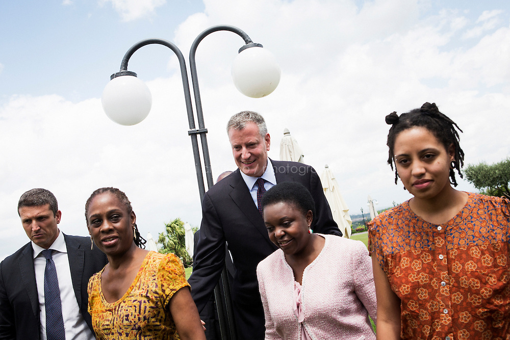 ROME, ITALY - 21 JULY 2014: Mayor of New York Bill De Blasio and C&eacute;cile Kyenge (center), former Italian Integration Minister and currently a member of the European parliament, leave afterr a photo spray with their respective families, at an exclusive social club in Rome, Italy, on July 21st 2014.<br /> <br /> New York City Mayor Bill de Blasio arrived in Italy with his family Sunday morning for an 8-day summer vacation that includes meetings with government officials and sightseeing in his ancestral homeland.