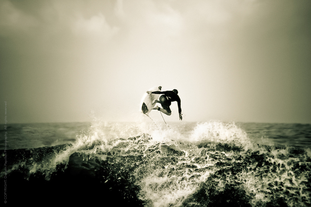 unidentifiable candid capture of surfer at the crest of a wave , Kona Reef, Hawaii