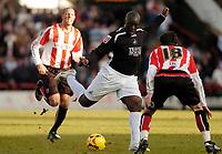 Photo: Leigh Quinnell.<br /> Brentford v Swansea City. Coca Cola League 1.<br /> 26/12/2005. Swanseas Adebayo Akinfenwa fires a shot past Brentfords Sam Tillen.