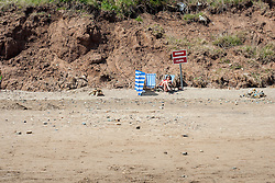 "A female Holiday maker with wind break and deckchairs sun bathes beside a ""Beware Dangerous Cliffs"" sign  on the Beach during the May Bank Holiday. Filey, North Yorkshire<br />  <br /> 21 May 2013<br /> Image © Paul David Drabble<br /> www.pauldaviddrabble.co.uk"