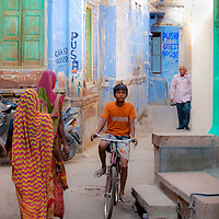 A Young Boy Rides Through An Alley Way In Varanasi, India