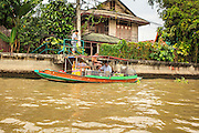 "17 NOVEMBER 2012 - BANGKOK, THAILAND:  A boat that serves a food stand makes a delivery to a home on a khlong or canal in the Thonburi section of Bangkok. Bangkok used to be known as the ""Venice of the East"" because of the number of waterways the criss crossed the city. Now most of the waterways have been filled in but boats and ships still play an important role in daily life in Bangkok. Thousands of people commute to work daily on the Chao Phraya Express Boats and fast boats that ply Khlong Saen Saeb or use boats to get around on the canals on the Thonburi side of the river. Boats are used to haul commodities through the city to deep water ports for export.    PHOTO BY JACK KURTZ"