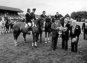 Col. Billy Ringrose, Chef d'Equipe of the Irish show jumping team, being presented with the Aga Khan Challenge Trophy (Nations Cup) by President Hillery. It was the first time since 1937 that Ireland got to keep the trophy, having won the competition three times in succession. The team comprised (l-r): Paul Darragh on Heather Honey; Captain Con Power on Rockbarton; James Kernan on Condy and Eddie Macken on Boomerang.<br />