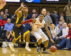 Feb 22, 2016; Morgantown, WV, USA; Iowa State Cyclones guard Monte Morris (11) dribbles past West Virginia Mountaineers guard Tarik Phillip (12) during the first half at the WVU Coliseum. Mandatory Credit: Ben Queen-USA TODAY Sports