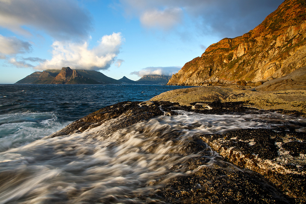 A long exposure capture of warm golden  afternoon light illuminating Cape Peninsula coastal mountains with background view of illuminated Chapmans Peak and Hout Bay. An unusual, low angle view  with a foreground of silky water flowing over rock formations overgrown with barnacles.