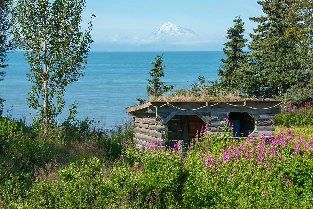 An old rustic building overlooking the ocean towards Mt. Redoubt in Alaska.