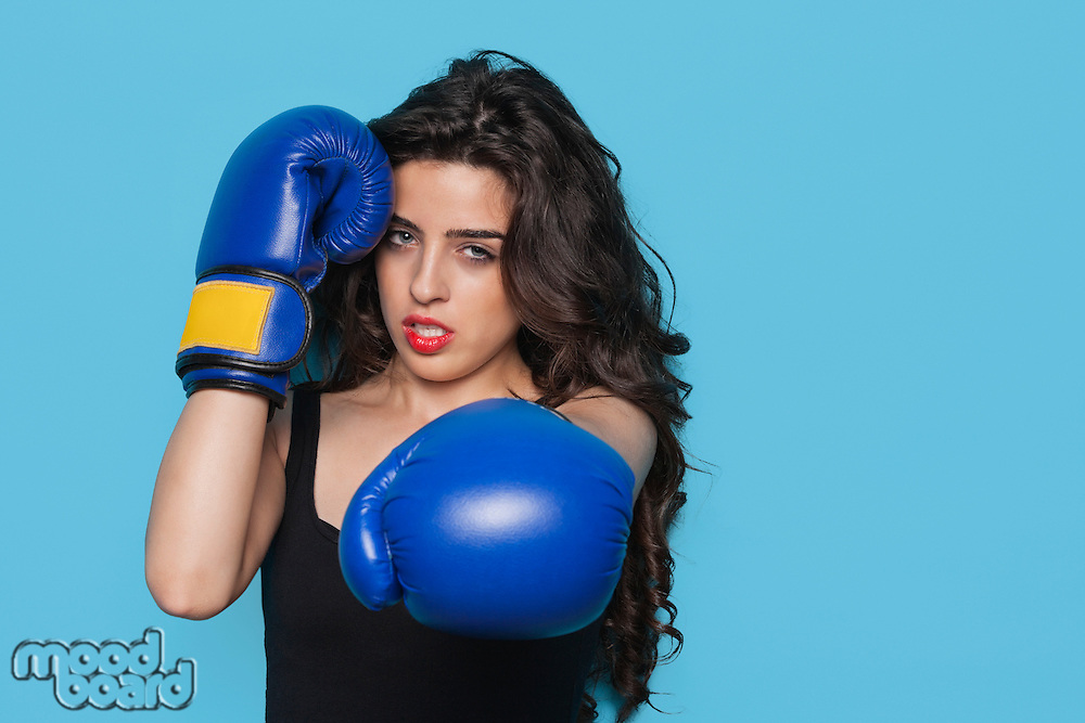 Portrait of an aggressive young woman wearing boxing gloves over blue background