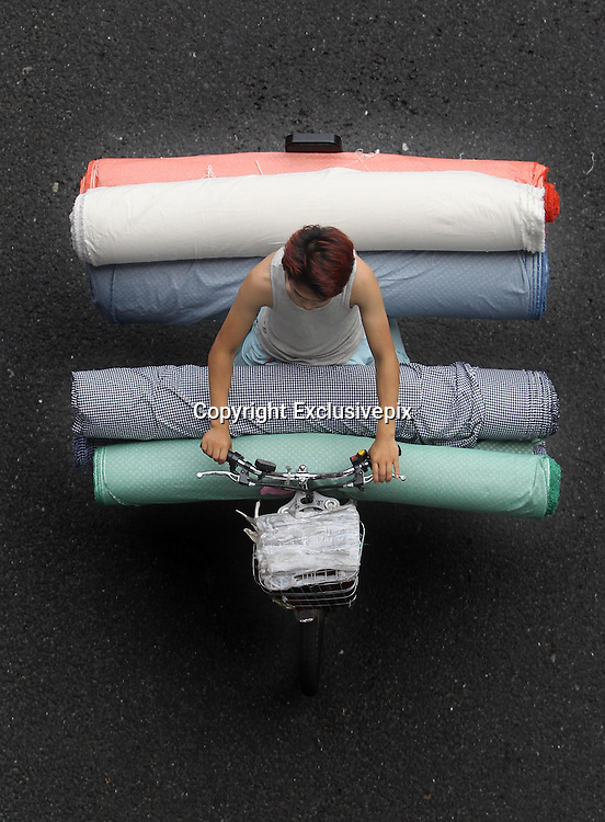 GUANGZHOU, CHINA - JUNE 04: (CHINA OUT) <br /> <br /> Life On The Tricycle<br /> <br /> A porter rides a tricycle carrying cloths and people at Guangzhou International Textile City on May 27, 2014 in Guangzhou, Guangdong Province of China. More than 1,500 tricycles are active in the business district.<br /> ©Exclusivepix