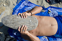 man holding large stone over his face while resting on the beach in Greece