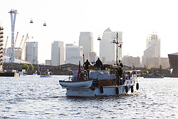 © Licensed to London News Pictures. 16/05/2015. London, UK. Dunkirk Little Ship, Bluebird of Chelsea parades in Royal Victora Dock this evening in front of Canary Wharf. Over 20 Dunkirk Little Ships have gathered in London toay before leaving in the morning to continue their journey to Dunkirk to mark the 75th anniversary of the Dunkirk Evacuations. Photo credit : Vickie Flores/LNP