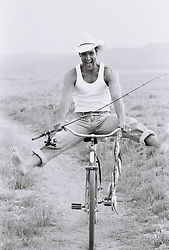 Man playfully riding bike along dirt path with fishing pole and string of fish