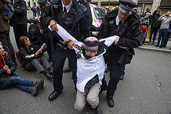 London, UK. 14 October, 2019. Police officers arrest a climate activist from Scientists for Extinction Rebellion who had blocked the busy junction at King William Street in front of London Bridge on the eighth day of International Rebellion protests across London. Today's activities were concentrated around the  City of London's finance district.