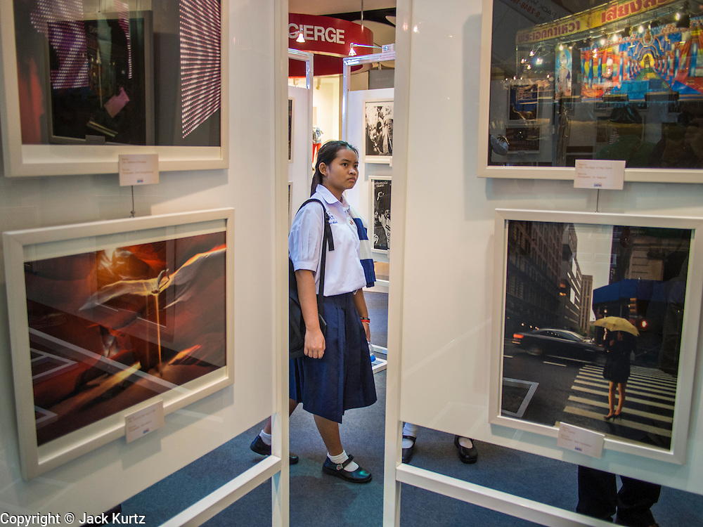 19 JULY 2013 - BANGKOK, THAILAND:    A Thai girl looks at photos hanging in a photo exhibit in CentralWorld in Bangkok. The US Embassy in Bangkok sponsored the photo exhibit, which celebrates 180 years of US-Thai diplomatic relations. There are 180 photos hanging in the show, 90 by American photographers in Thailand and 90 by Thai photographers in the United States. The show, which opened July 19, is hanging in CentralWorld, a large mall in Bangkok, and is touring Thailand when it concludes its Bangkok run on July 21.  PHOTO BY JACK KURTZ