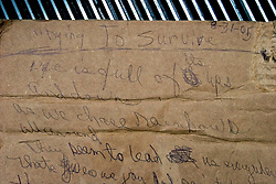 01 Sept, 2005. New Orleans, Louisiana.<br /> Mass evacuation of New Orleans begins. A poem handed to us by an evacuee as they headed to the busses taking them out of New Orleans to destinations unknown.<br /> The poem by Lethia Guichard is titled; <br /> 'Dying to Survive.'<br /> Life is full of its ups and downs,<br /> As we chase rainbows all around,<br /> They seem to lead us everywhere,<br /> That gives us joy and pain to bear,<br /> Those in charge are not to be found,<br /> Faith not a face stayed or came to town,<br /> leaving us in this fishbowl of hell water to drown.<br /> Photo©; Charlie Varley/varleypix.com