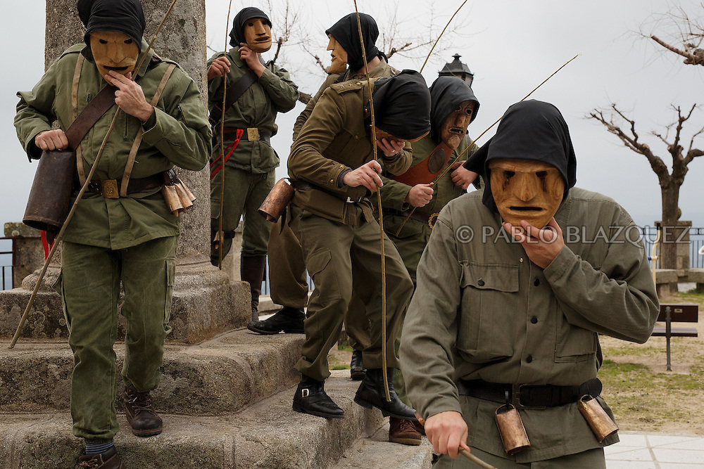 The Machurreros from Pedro Bernardo walk in a park during Carnival on February 6, 2016 in Pedro Bernardo, in Avila province, Spain. The origins of this pagan festival are unknown. The Machurreros wear wood masks, a military dress, black handkerchief, cowbells, and hold wicker stick. The festival disappeared after Dictator Franco forbid carnival festivals in 1937, but it was recently recovered. Before disappearing, male villagers after the military service, used to dress as Machurreros as they run along the streets scaring children and adults with their wicker stick to bring fertility to the land and expel the evil spirits. (© Pablo Blazquez)
