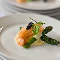 A tasting plate of large shrimp topped with caviar on a bed of asparagus and lemon cream sauce at FoodShare's Recipe for Change 2011