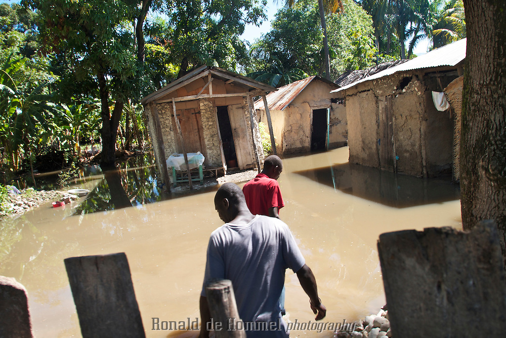 Landless workers in the agricultural zone, Artibonite, of Haiti wade to their flooded houses after a night of monsoonal rains. The floodings happen regularly because the drainage canals can not handle the large amounts of water that come down the deforested hills in the area.