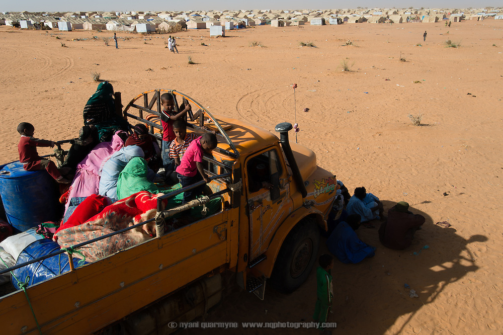 A truck loaded with Malian refugees and their meagre belongings sits parked in the heat on the edge of the Mbera refugee camp in Mauritania while it waits for the rest of the convoy to catch up, on 6 March 2013. According to local NGO, ALPD, 825 refugees arrived in this convoy, packed into three trucks and an assortment of four wheel drive pick-ups.