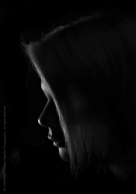 studio black & white portrait, female profile in silhouette