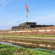 The Vietnamese flag flies over the citadel at the Imperial City in Hue, Vietnam. A self-enclosed and fortified palace, the complex includes the Purple Forbidden City, which was the inner sanctum of the imperial household, as well as temples, courtyards, gardens, and other buildings. Much of the Imperial City was damaged or destroyed during the Vietnam War. It is now designated as a UNESCO World Heritage site.