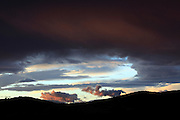 dramatic colorful cloud formations contrasting with a silhouette hilly landscape