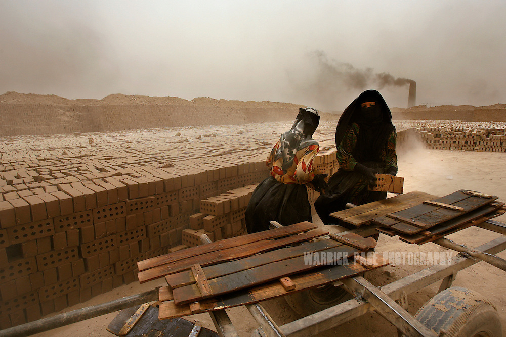 IRAQ, NARWAN - JULY 1: Women transfer bricks from donkey-drawn carts to drying stacks at the Narwan brick factory, July 1, 2008 in Narwan, Iraq. Twenty miles east of Baghdad, the 170+ small brick factories employ about 30,000 Iraqis, shaping mud into bricks and fire them in kilns burning heavy fuel oil that produces acrid, black smoke visible from satellite imagery 50 miles above the earth's surface. The brick factory employs seasonal workers, many of whom are children - some are as young as four - in highly toxic conditions offering minimal food and water. Respiratory problems are common amongst the workers and children, with no medical personal available to treat them. (Photo by Warrick Page)