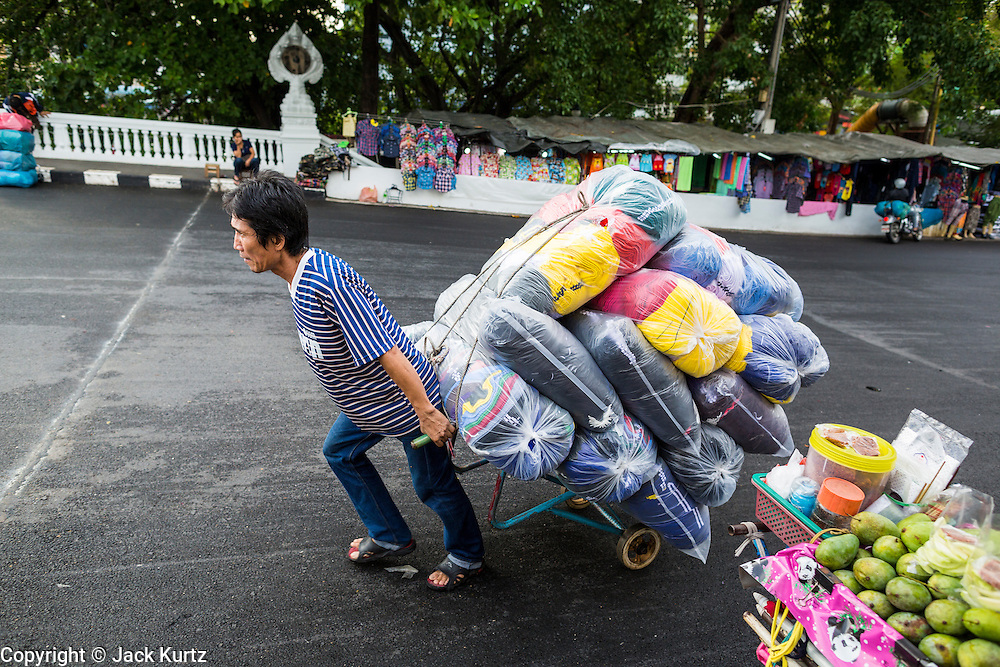06 JUNE 2013 - BANGKOK, THAILAND:   A porter hauls clothes up Krung Kasem Rd to Bobae Market in Bangkok. Bobae Market is a 30 year old market famous for fashion wholesale and is now very popular with exporters from around the world. Bobae Tower is next to the market and  advertises itself as having 1,300 stalls under one roof and claims to be the largest garment wholesale center in Thailand.       PHOTO BY JACK KURTZ