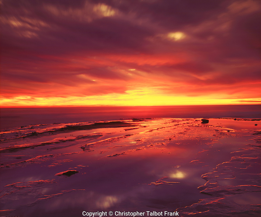 Amazing colors radiate from my photo of a vibrant Pacific Ocean sunset.  Vivid yellow, orange, red, and purple clouds reflect in a tide pool.