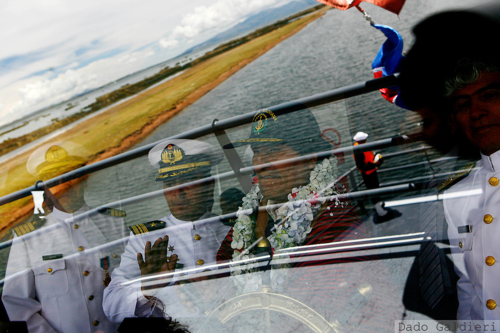 Bolivia's President Evo Morales, third from left, is seen through a glass as he takes the helm of a Bolivian built vessel during the inauguration of the new ship in Guaqui, Bolivia, Friday, Feb. 13, 2009. The ship will be use to patrol the Titicaca Lake.