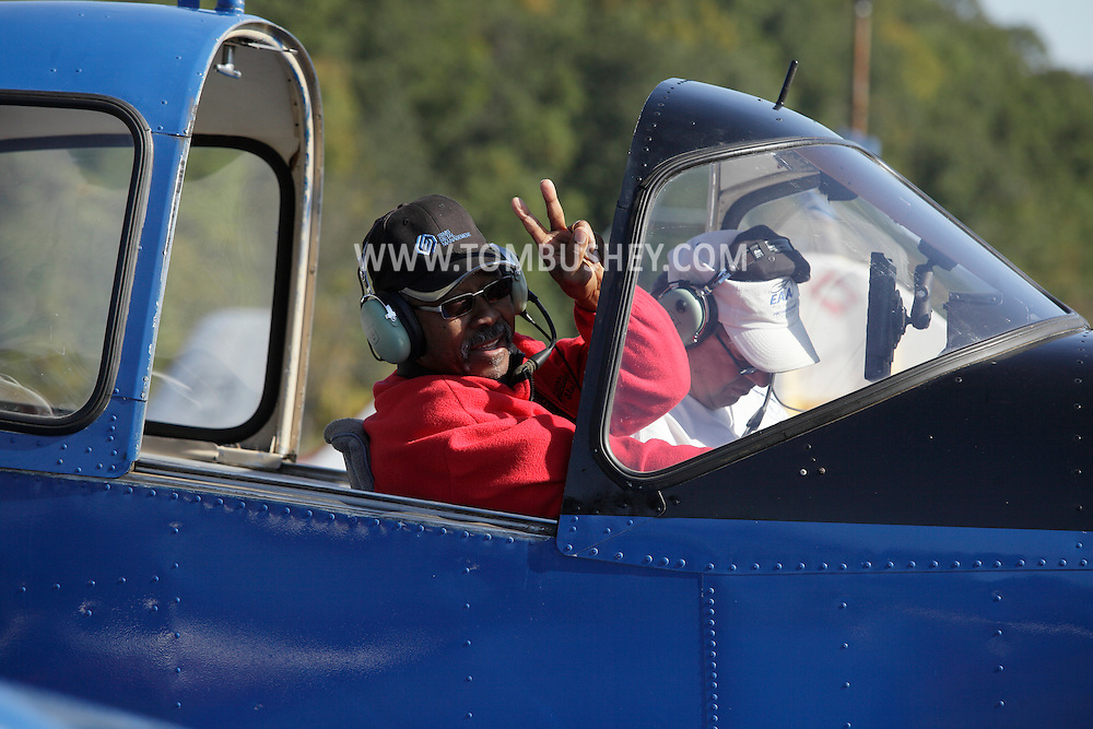 Wurtsboro, New York - A passenger in an airplane waves while the pilot prepares for takeoff at Wurtsboro Airport during the annual Fly In - Drive- In Breakfast on Oct. 9, 2011.