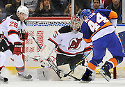 New York Islanders' Freddy Meyer shoots  past New Jersey Devils goalie Yann Danis as Devils' Martin Skoula tries to defend at Nassau Coliseum in N.Y. (AP Photo/Kathy Kmonicek)