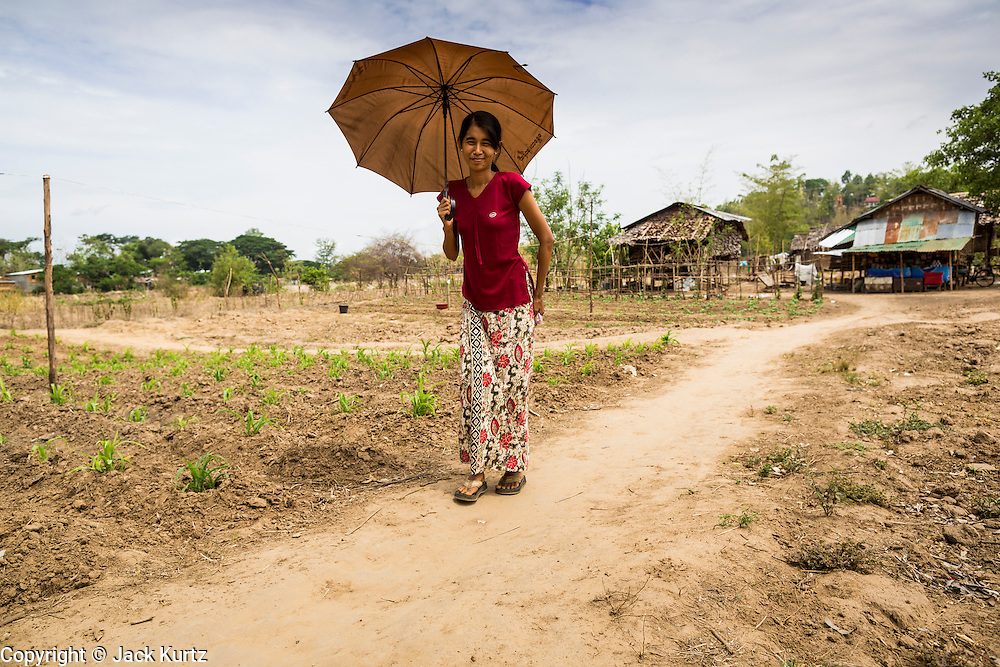 25 MAY 2013 - MAE SOT, TAK, THAILAND:  A Burmese woman walks through an unofficial village of Burmese refugees north of Mae Sot, Thailand. They live on a narrow strip of land about 200 meters deep and 400 meters long that juts into Thailand. The land is technically Burma but it is on the Thai side of the Moei River, which marks most of the border in this part of Thailand. The refugees, a mix of Buddhists and Christians, settled on the land years ago to avoid strife in Myanmar (Burma). For all practical purposes they live in Thailand. They shop in Thai markets and see their produce to Thai buyers. About 200 people live in thatched huts spread throughout the community. They're close enough to Mae Sot that some can work in town and Burmese merchants from Mae Sot come out to their village to do business with them.   PHOTO BY JACK KURTZ