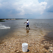 Paul Blair, of Ridgeland, uses a cast net while fishing with his family along the Broad River Bridge near Lemon Island, on June 15, 2014.