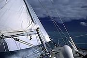 close-up of sailboat heeling in strong wind; manisail reefed; close hauled; aqua water; British Virgin Islands; Caribbean