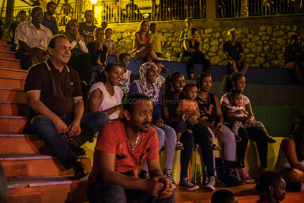 Riace's three-term mayor, Domenico Lucano (on the left) is watching a live show in the main square of Riace with a group of people from Horn of Africa. In the past 18 years Riace has welcomed more than 6,000 migrants. As they arrived in Riace, an aging place with high unemployment, the mayor sensed an opportunity to revive what was quickly becoming a ghost town. He offered refugees abandoned apartments and job training.  RIACE (ITALY) 31/07/16
