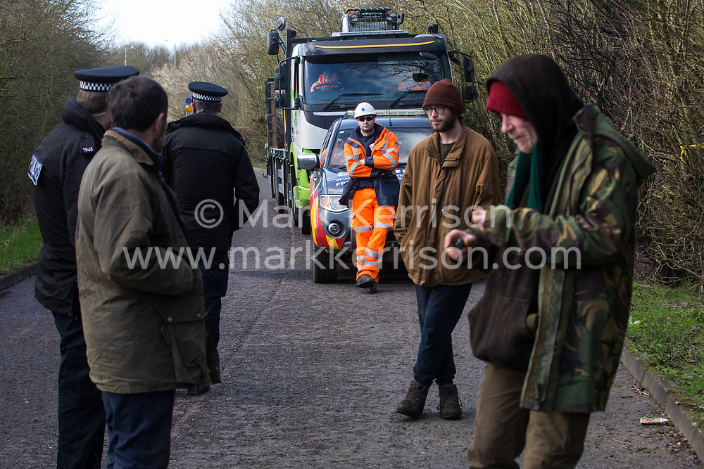 Denham, UK. 11 February, 2020. Thames Valley Police officers speak to environmental activists from Extinction Rebellion, Stop HS2 and Save the Colne Valley 'slow walking' in front of a large truck transporting a JCB forklift truck to a HS2 site at Denham in the Colne Valley. Contractors working on behalf of HS2 are rerouting electricity pylons through a Site of Metropolitan Importance for Nature Conservation (SMI) in conjunction with the high-speed rail link.