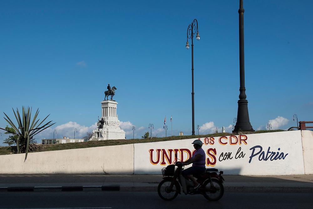 Havana, Cuba -  October 2015: A motorcyclist rides on Avenida del Puerto in front of a mural.