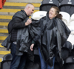 St Mirren fans cover up from the rain before the Ladbrokes Scottish Premier League match at St Mirren Park, St Mirren.