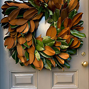 Christmas Wreath with green leaves decorations on front door in Greenwich Village.<br /> <br /> The tradition of hanging wreath during Christmas is essentially a Christian ritual done during the Christmas season.<br /> <br /> Traditionally, the Christmas wreaths were made of evergreen leaves, which are still symbolize the permanence of life. <br /> <br /> A traditional wreath is a circle, which means that there is no beginning or end and that God is eternal.