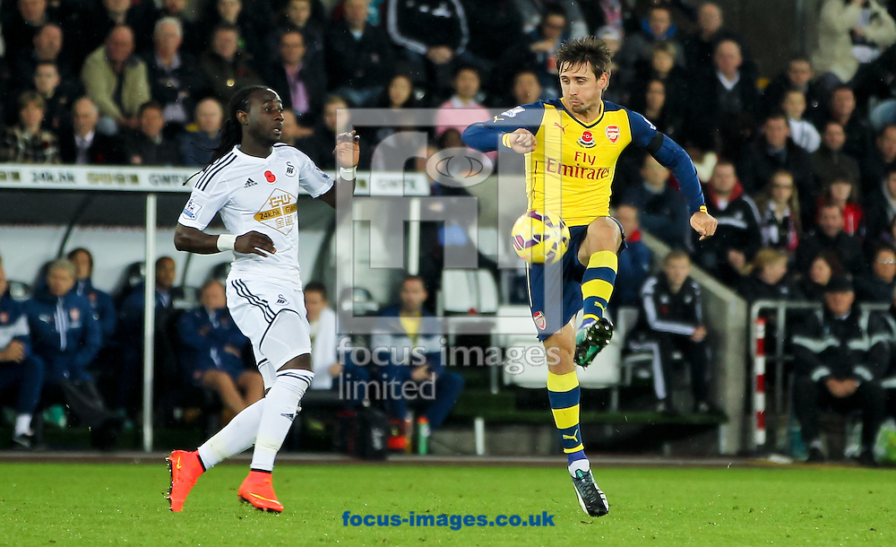 Marvin Emnes (left) of Swansea City puts Nacho Monreal (right) of Arsenal under pressure as he controls the ball in the air during the Barclays Premier League match at the Liberty Stadium, Swansea<br /> Picture by Tom Smith/Focus Images Ltd 07545141164<br /> 09/11/2014