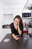 Happy young woman reading text message on smart phone in kitchen